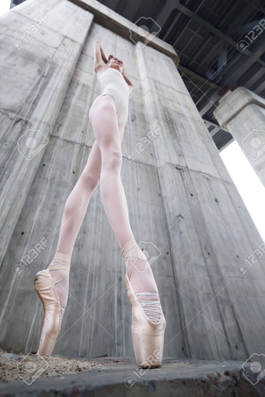 Slim ballerina on a background of the concrete pillars of the..
