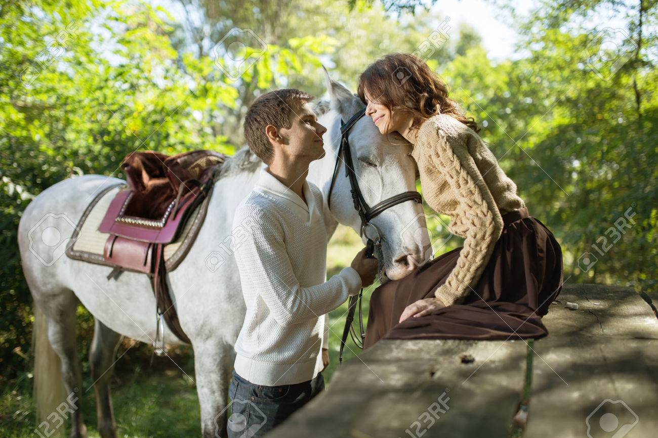Jeune Couple Dans L Amour Avec Un Cheval Blanc Sur Une Promenade A L