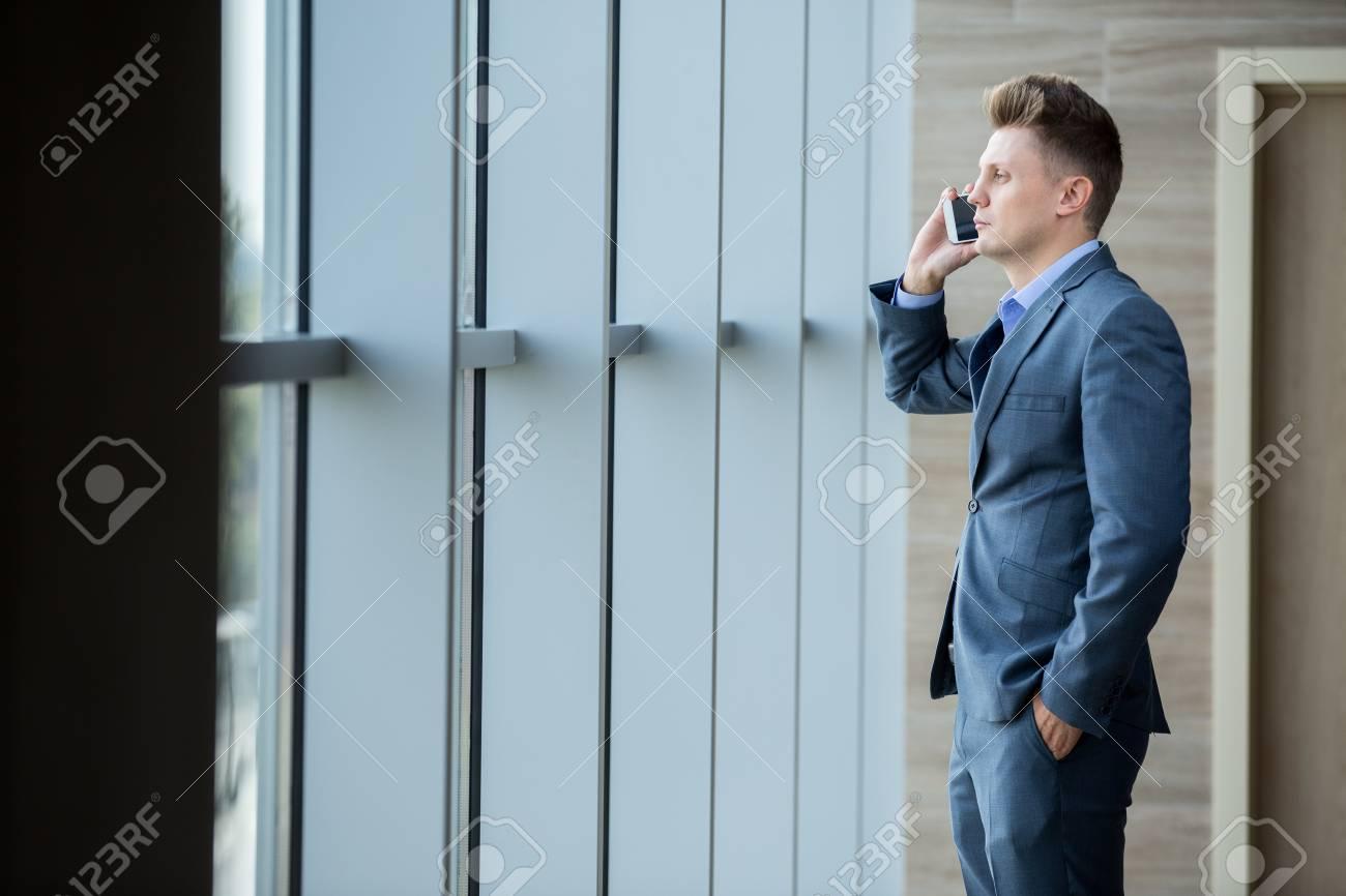 De Rubia La El Por Hombre Oscuro Negocios Hablando Un Teléfono Traje En Mirando Ventana Foto Archivo wdI4xqBw