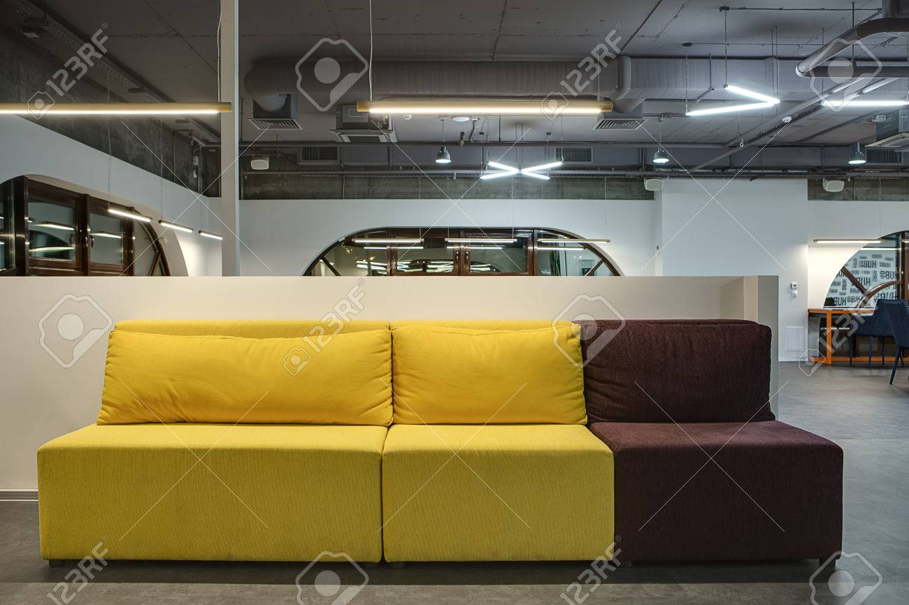 Yellow-brown Sofa With Pillows On The White Low Wall Background ...