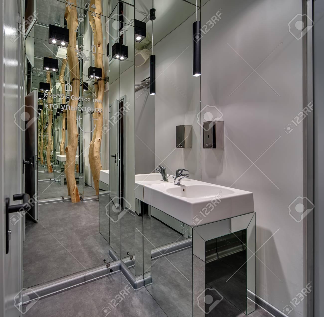Grand Miroir D Entrée entrée de la salle de bain avec un grand miroir côté gauche et une  décoration d'arbre sur un fond réfléchi. il y a un évier blanc et un  distributeur