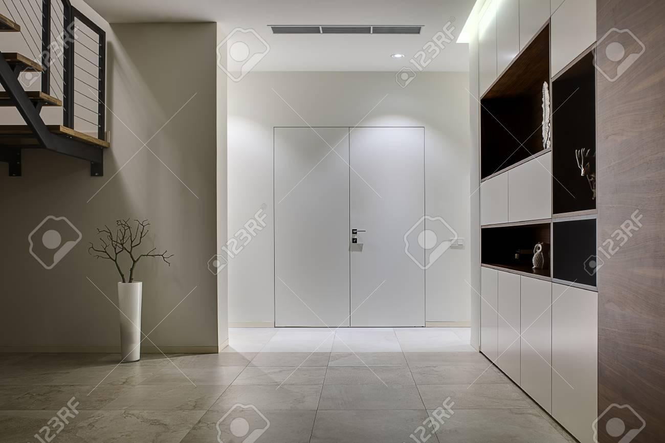 Sala con pareti chiare e piastrelle di luce sul pavimento sulla