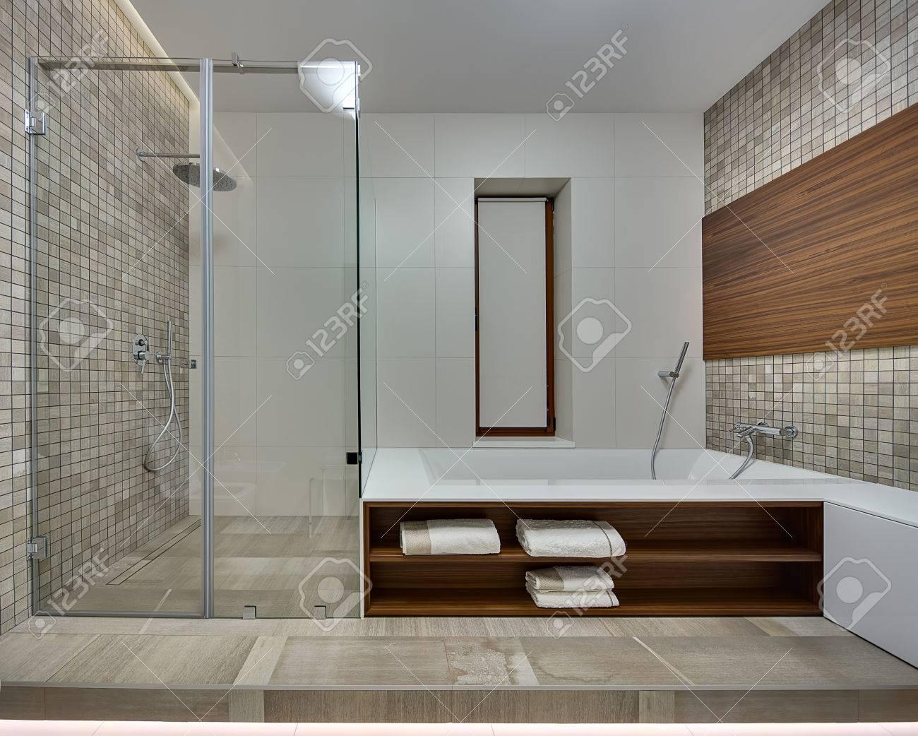Badezimmer In Einem Modernen Stil Mit Hellen Fliesen An Der Rückwand. Die  Seitenwände Ist Mit Braun Beige Mosaik Und Einer Holzplatte Dekoriert.