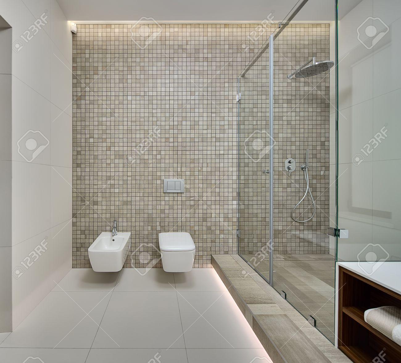 Salle d\'eau dans un style moderne. Paroi arrière décorée de mosaïque beige.  Sur le mur arrière, il y a un bidet blanc, toilette et commutateurs blanc.  ...