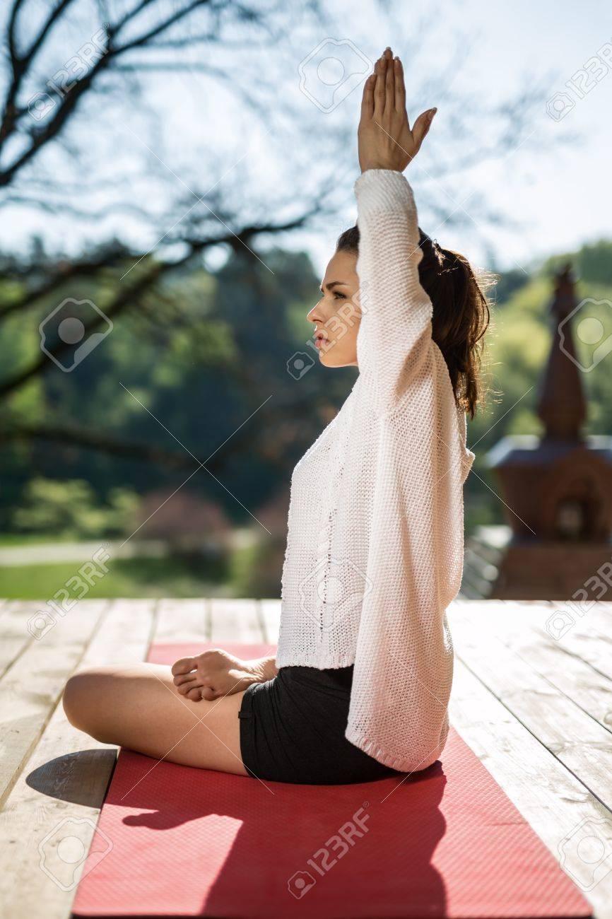 Muchacha Pacífica A Yoga En La Terraza De Madera En El Fondo De La Naturaleza Ella Se Sienta En El Lado De Loto En La Estera De Yoga Rojo Y Extiende