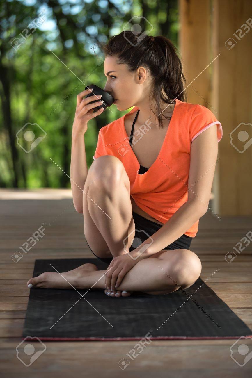 Chica Increíble Se Sienta En La Estera De Yoga Negro En La Terraza De Madera En El Fondo De La Naturaleza Su Cabeza Se Gira A La Derecha El Pie