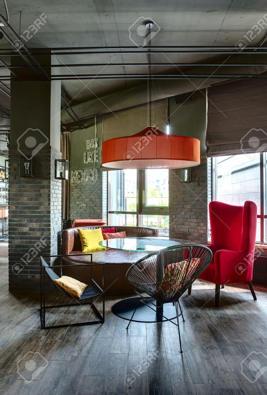 Cuscini Su Divano Marrone camera in un ristorante messicano in stile loft. c'è un tavolo rotondo di  vetro con sedie nere, una poltrona e un divano cremisi marrone. su di loro