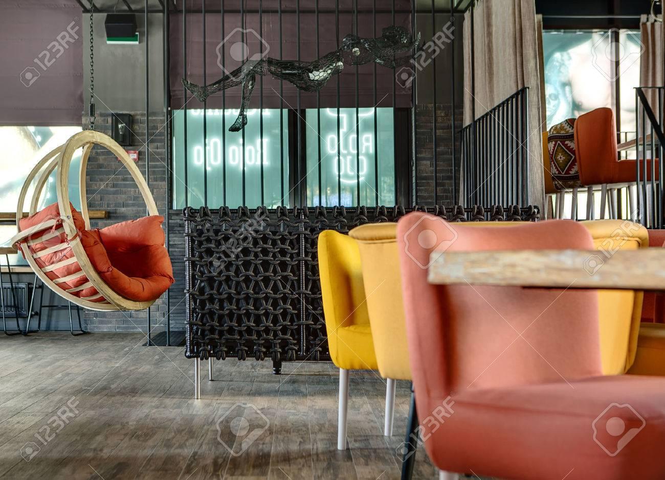 Il Y A Une Table En Bois Chaises Multicolores Un Canap Osier Noir Et Pendaison Chaise Bascule Avec Oreiller Rouge