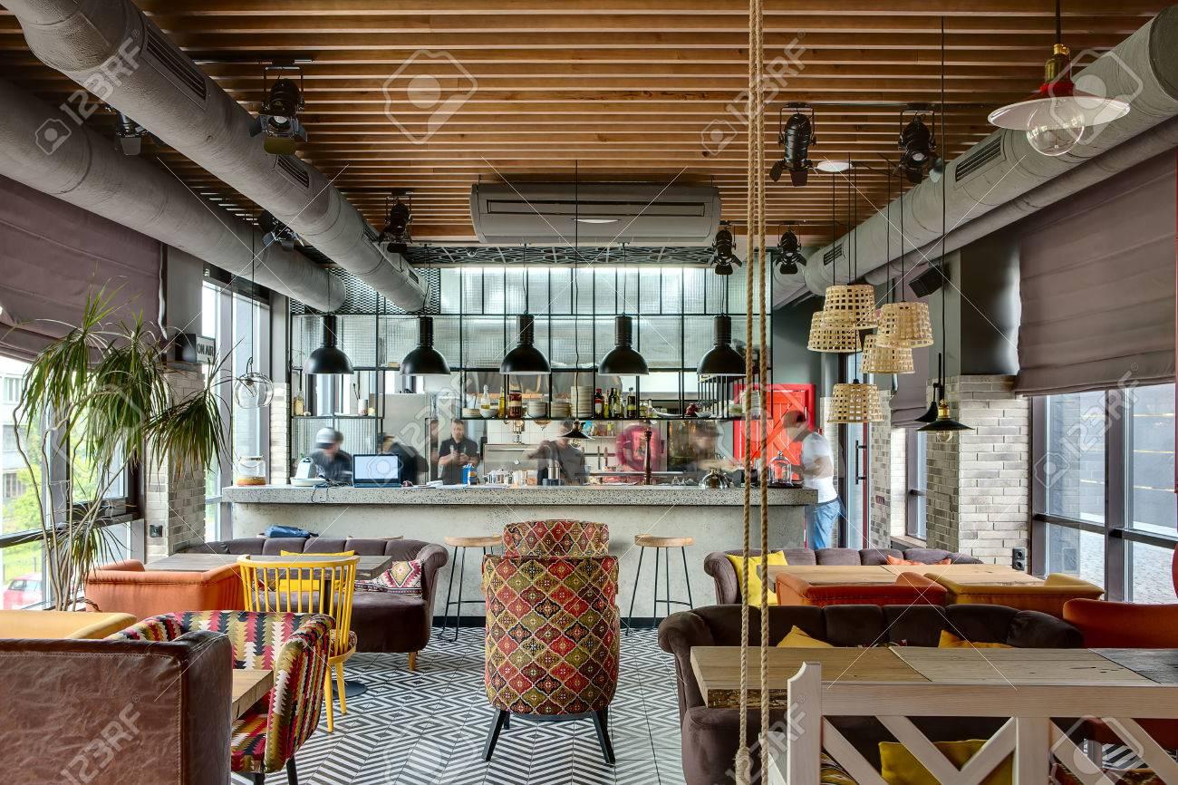 fantastische interieur in einem loft stil in einem mexikanischen restaurant mit offener kche im hintergrund vor der kche gibt es holztische mit bunten - Loft Stil