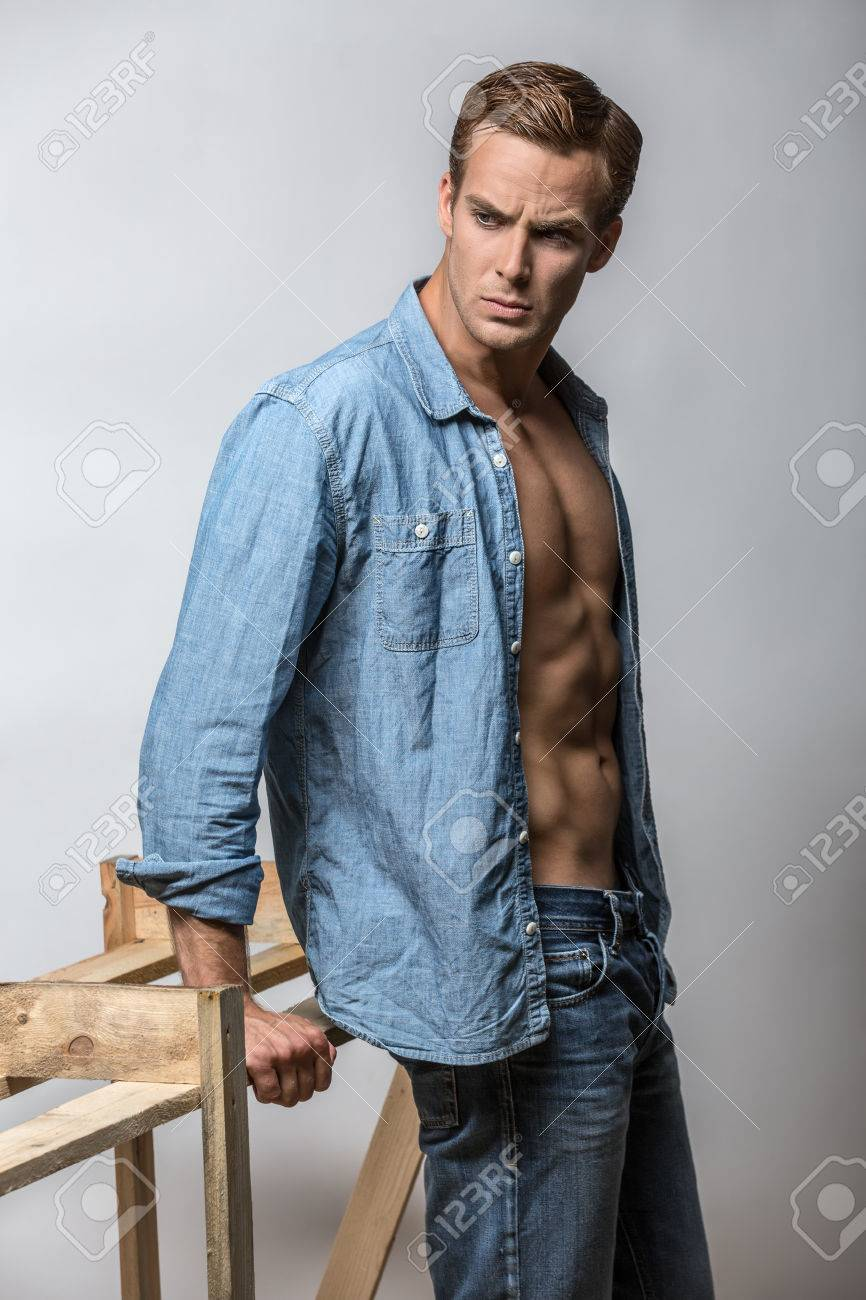 b19fd3cf Muscular guy in a blue denim unbuttoned shirt and blue jeans stands in the  studio on