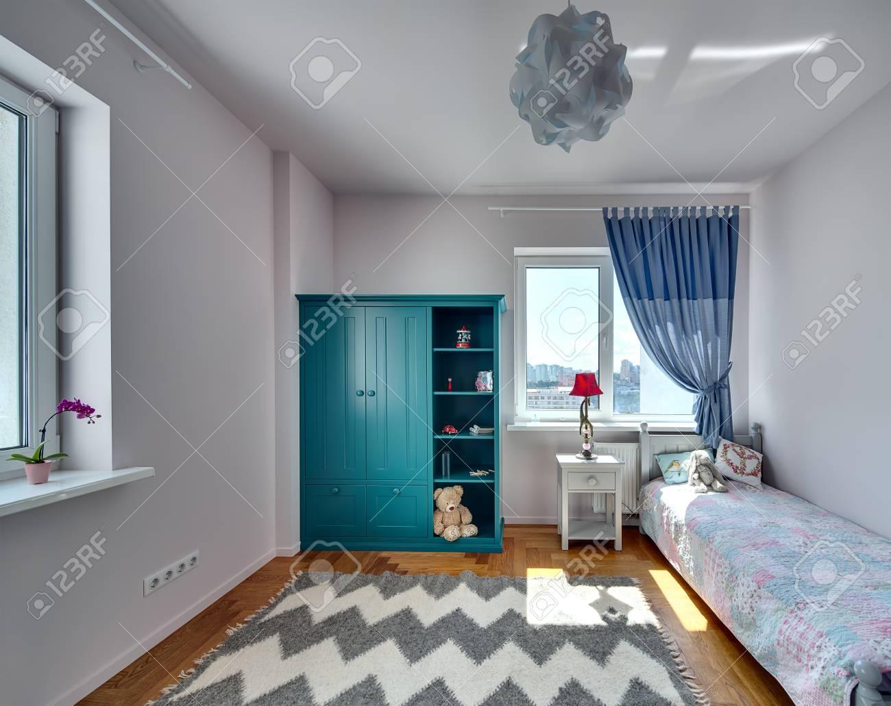 Camera per bambini con pareti chiare e un parquet con moquette sul