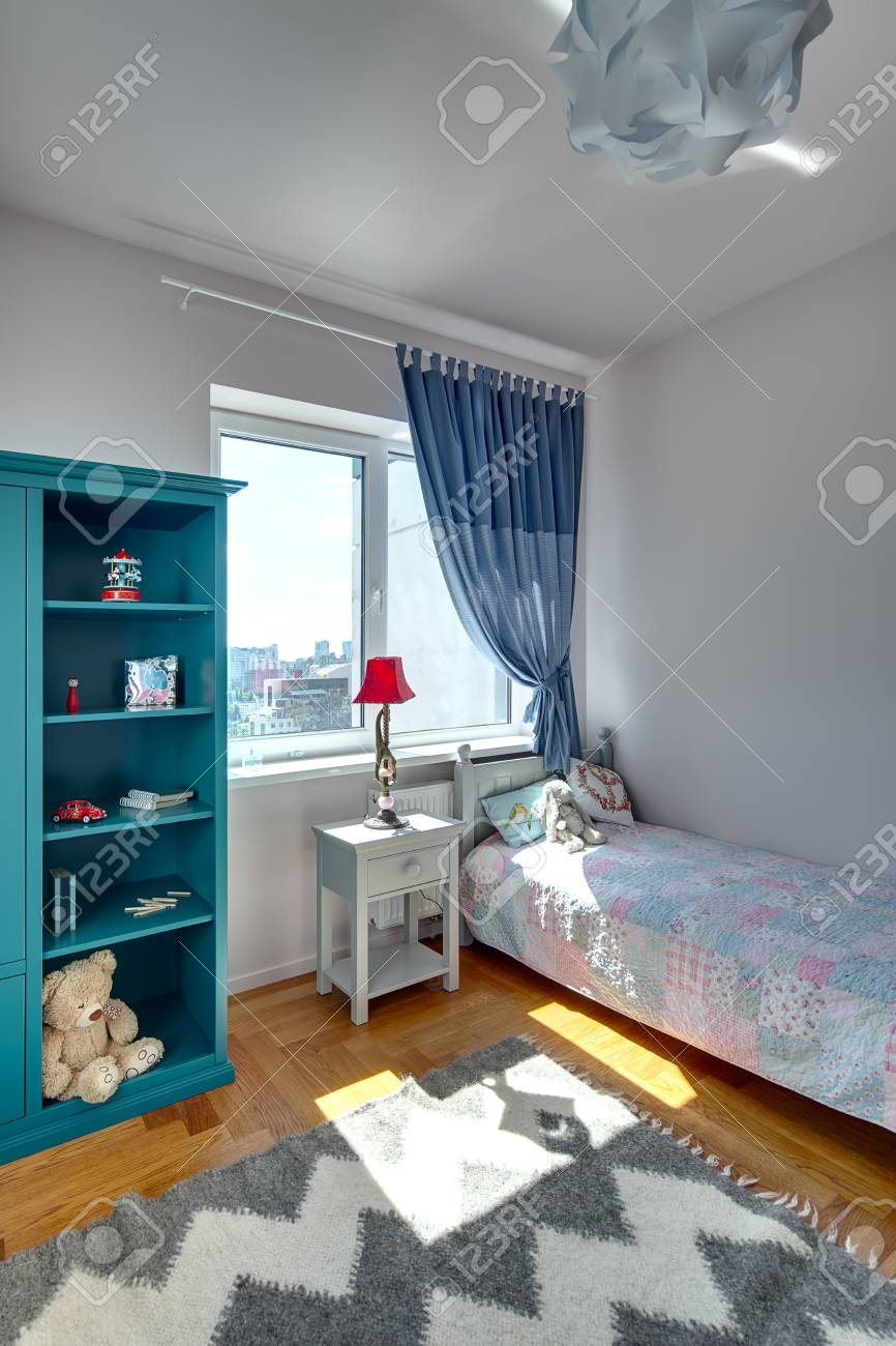 Children\'s bedroom with white walls and a parquet with carpet..