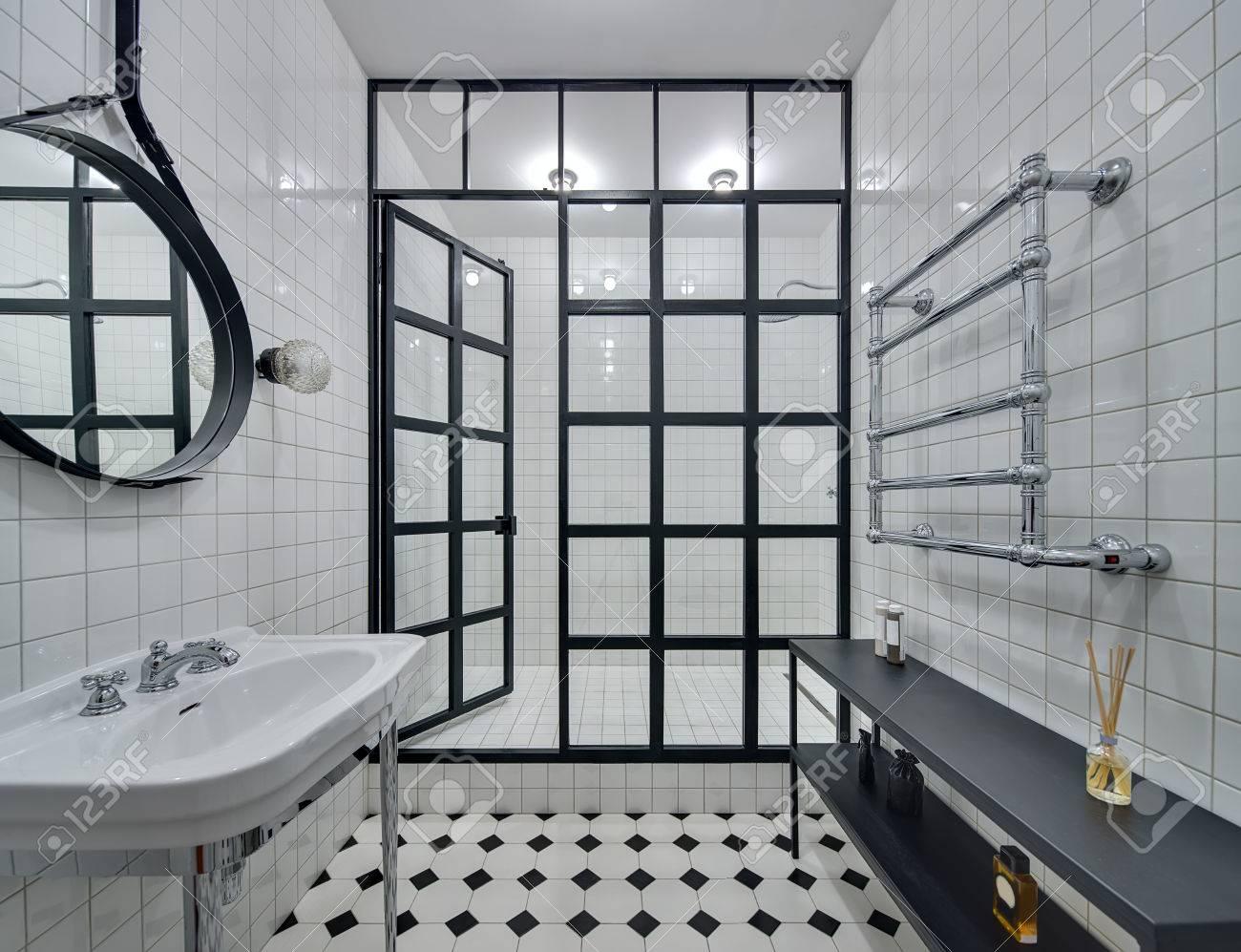 cuarto de bao con paredes de azulejos blancos hay lavabo blanco negro espejo