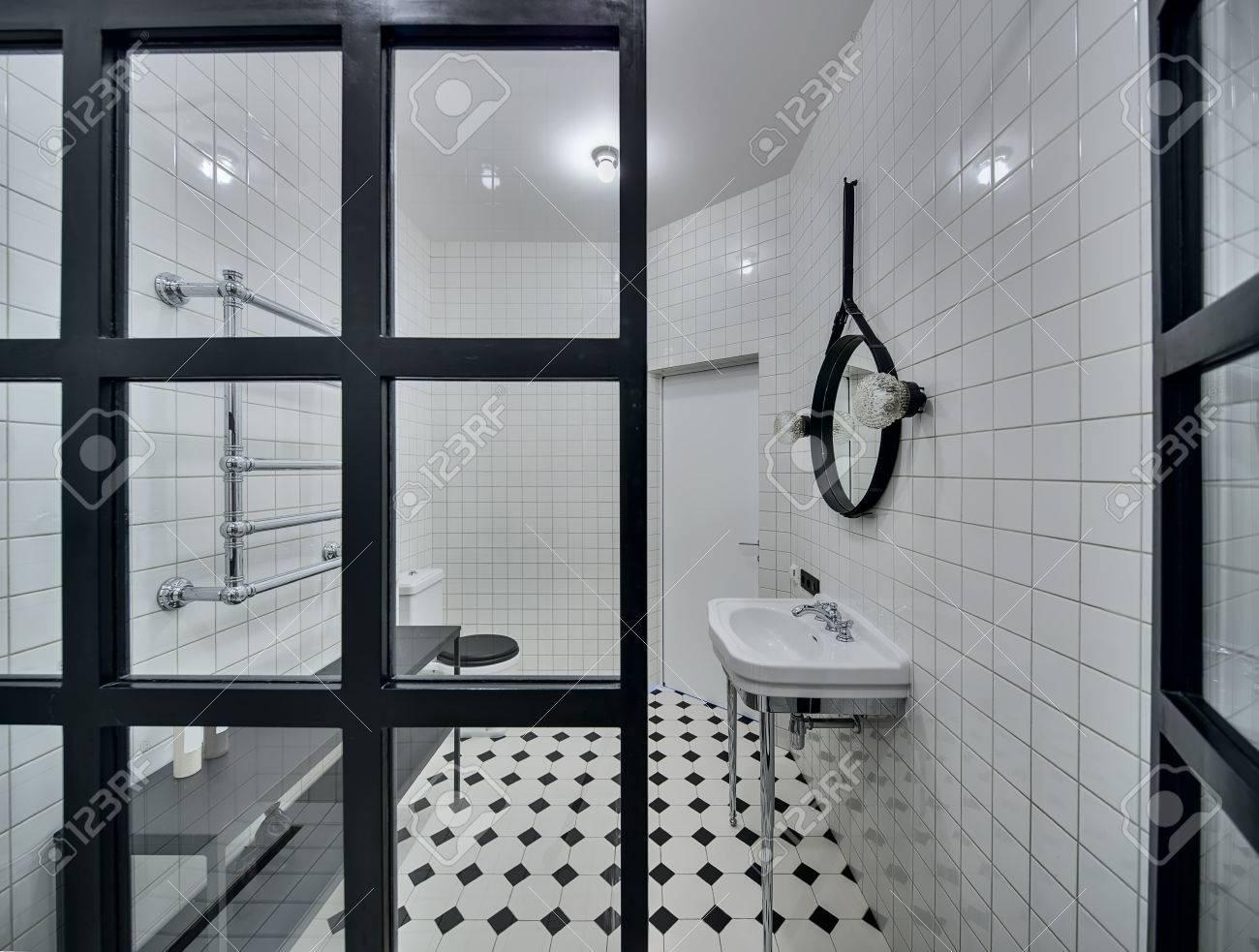 Moderno cuarto de baño con paredes de azulejos blancos. Hay lavabo blanco,  negro espejo, lámparas, mampara de cristal, inodoro blanco y negro, estante  ...