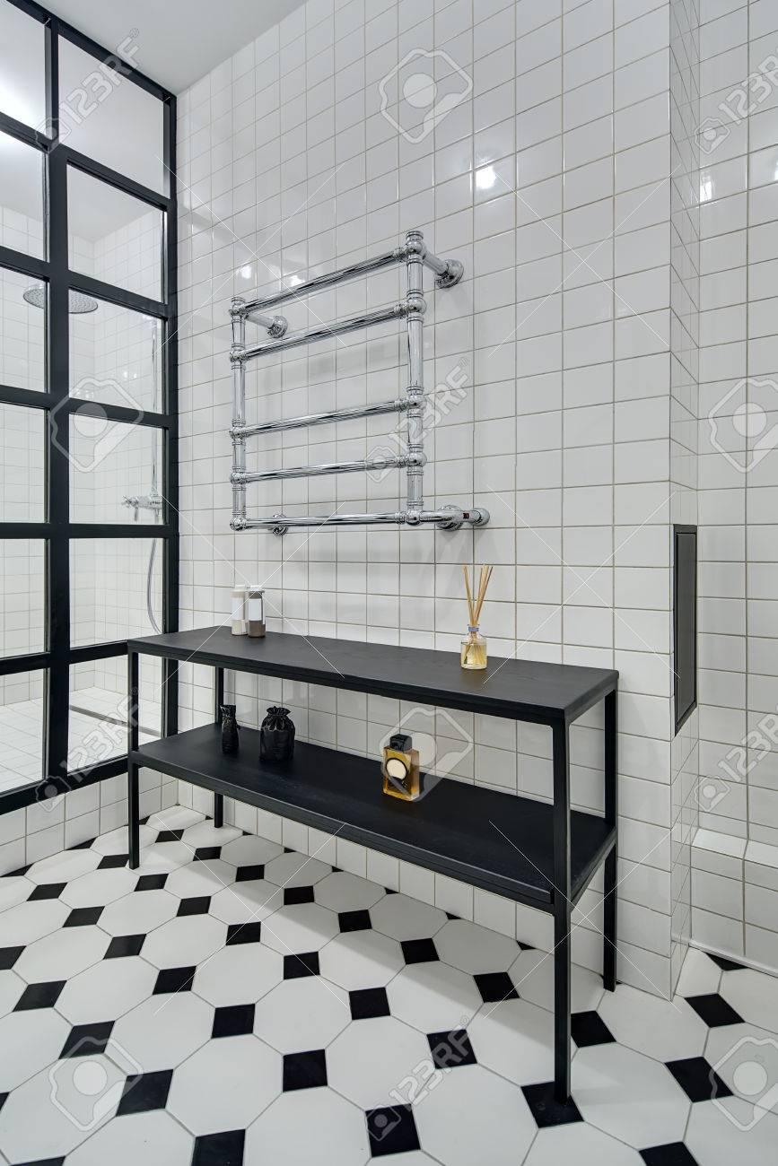 elegante bao con paredes de azulejos blancos hay ducha con mampara de vidrio negro de