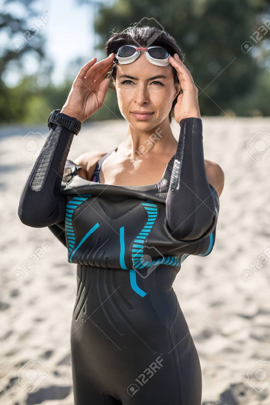 Pretty sportive woman in a dark swimrun suit stands on the sand outdoors.  She holds 396057b2b01b