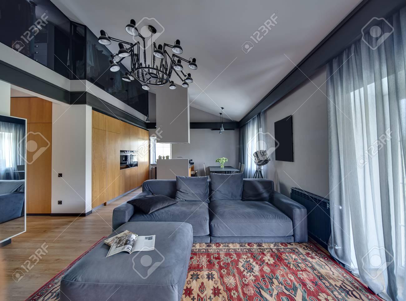 Archivio fotografico camera in stile moderno con pareti chiare e parquet con tappeto rosso sul pavimento cè divano blu con cuscini isola cucina