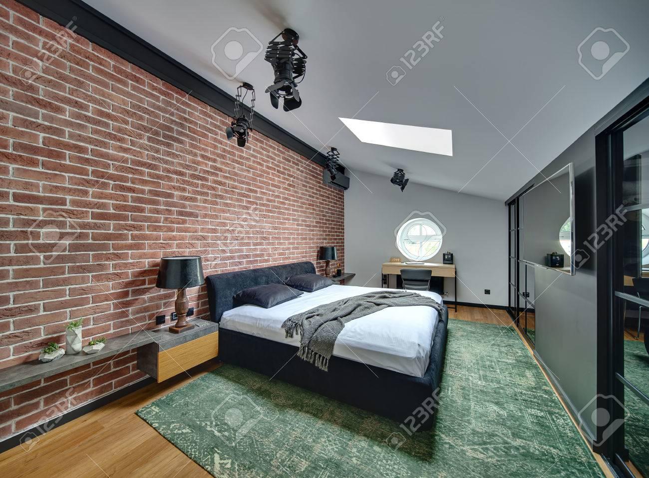 Stilvolles Schlafzimmer Im Modernen Stil Mit Mauer Und Parkett Mit Grünem  Teppich Auf Dem Boden. Es Gibt Bett, Racks Mit Lampen Und Dekorationen, ...