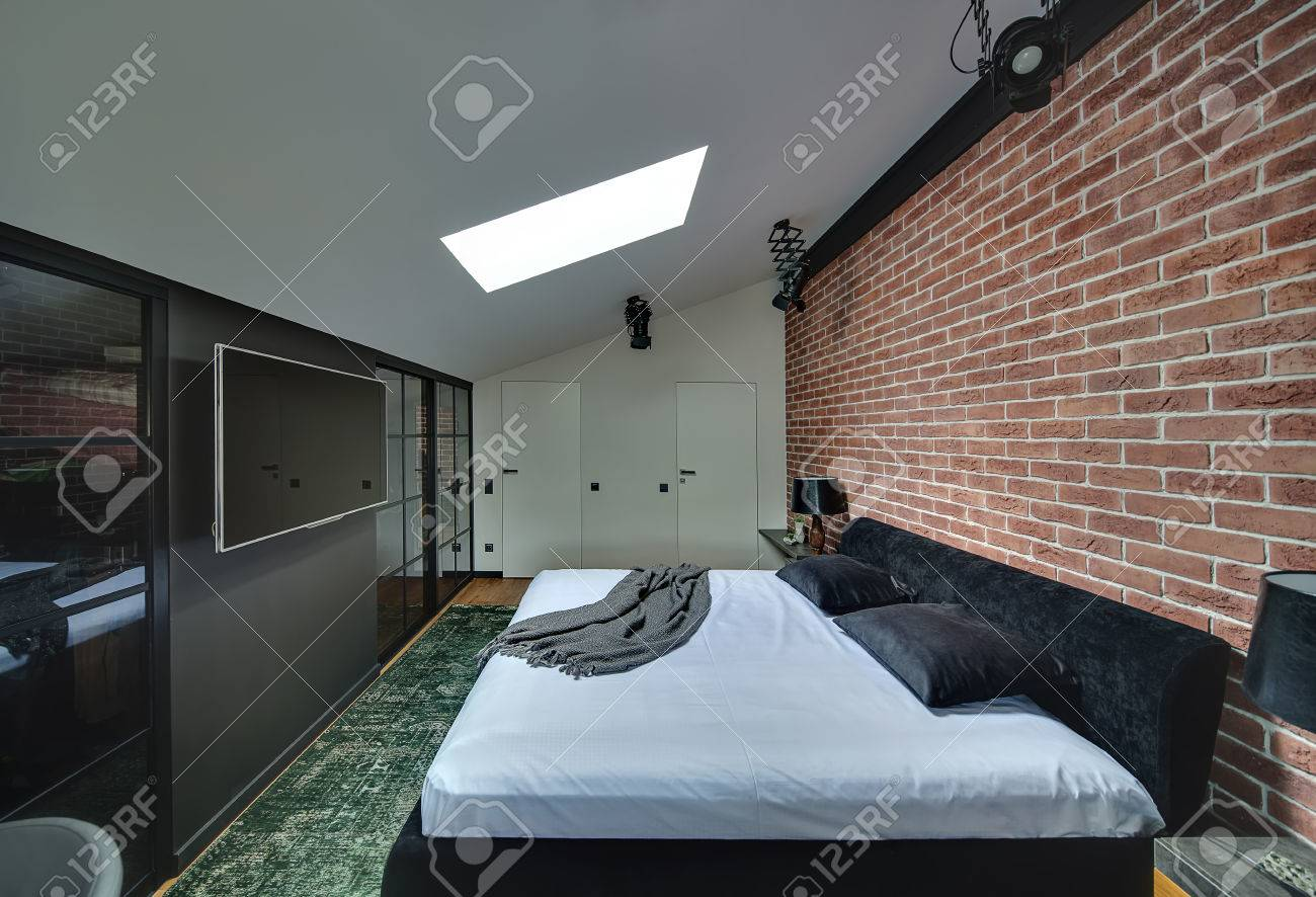 . Contemporary bedroom with brick wall and parquet with green carpet