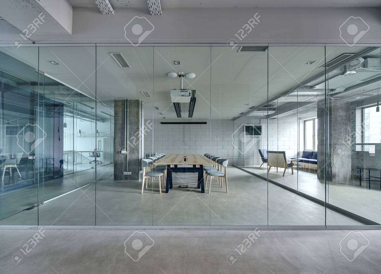 Office in a loft style with white brick walls and concrete columns. There is a meeting zone with a large wooden table with gray chairs and glass partitions. Above the table there is a projector. - 65626778