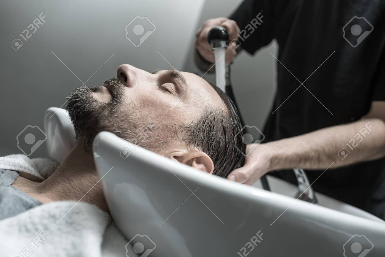 Man With Closed Eyes And A Beard Lies On The White Sink In The ...