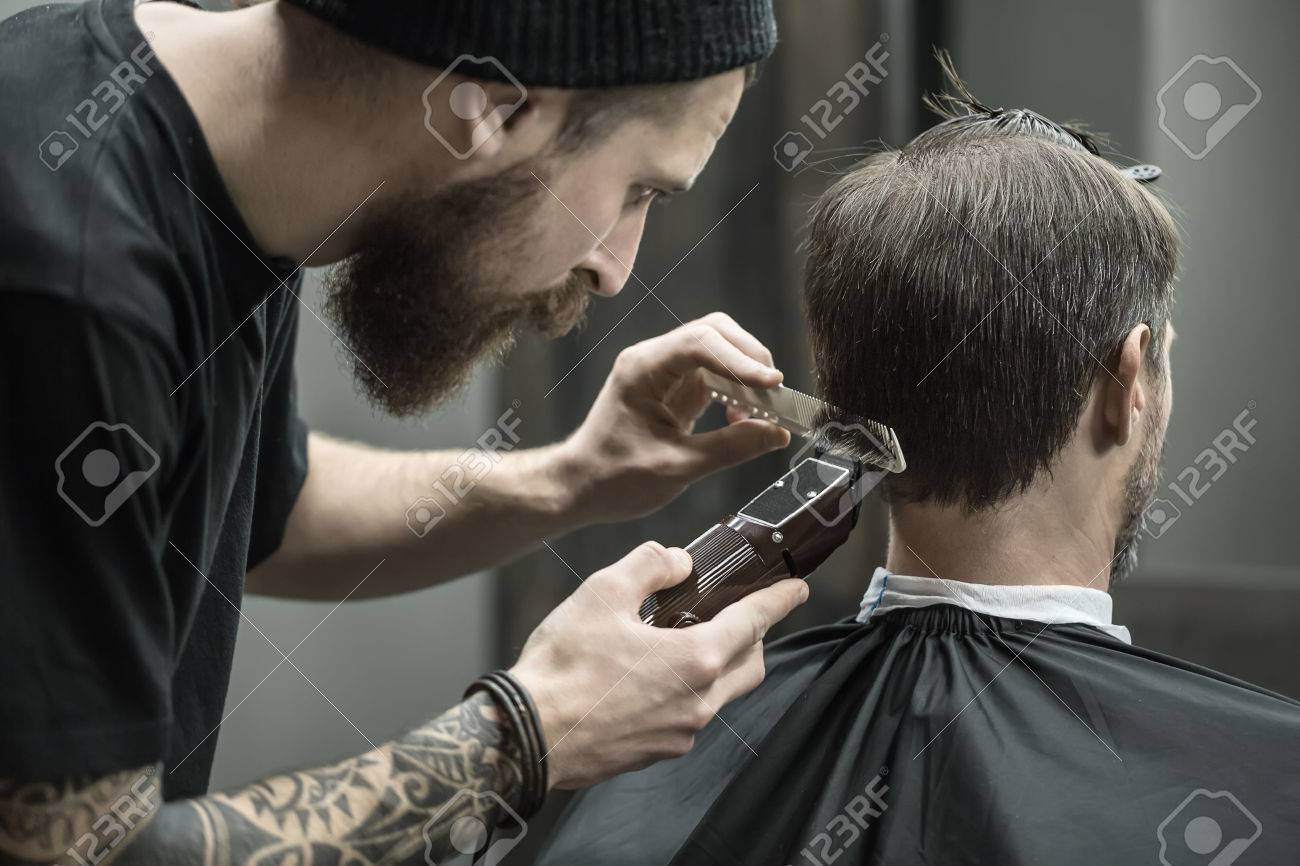 Incomparable Barber With A Beard And A Tattoo Is Cutting The