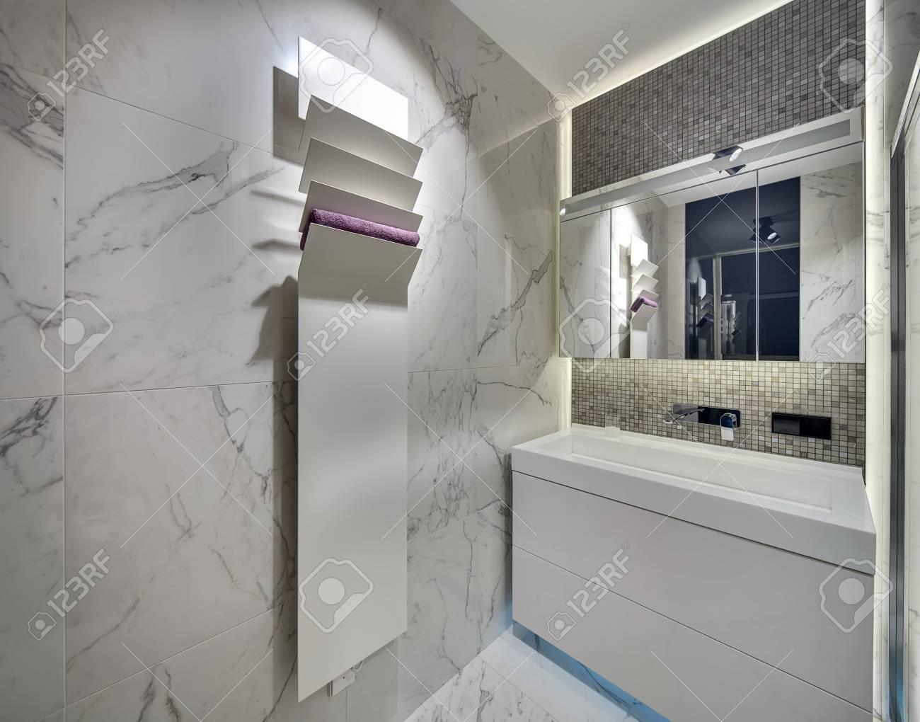 Bagno Con Mosaico Bianco bagno moderno con piastrelle chiare sulle pareti e sul pavimento. c'è un  lavandino bianco con un rubinetto cromato e uno specchio, un supporto  bianco
