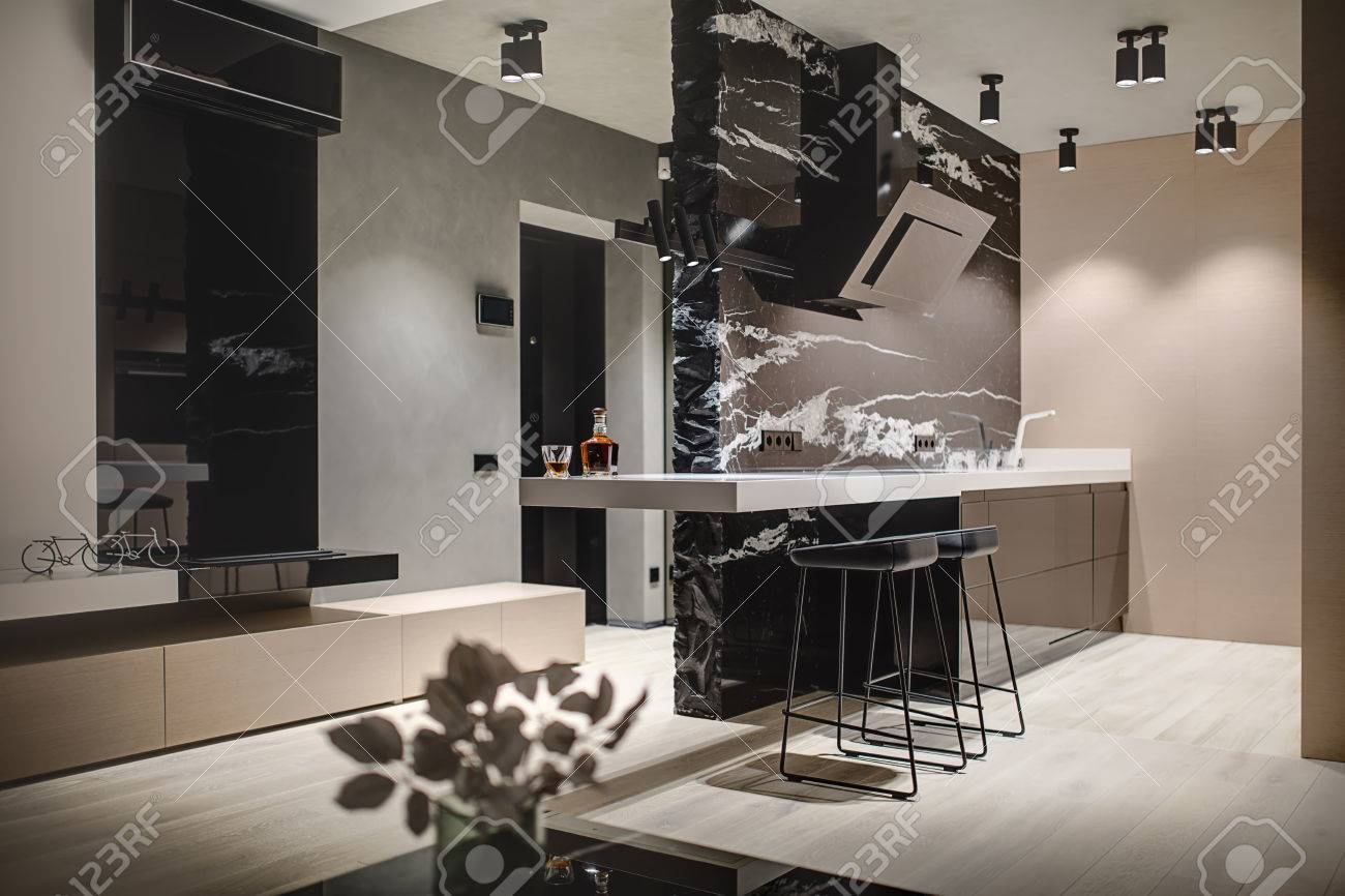 Modern style kitchen island with a black marble wall with a kitchen..