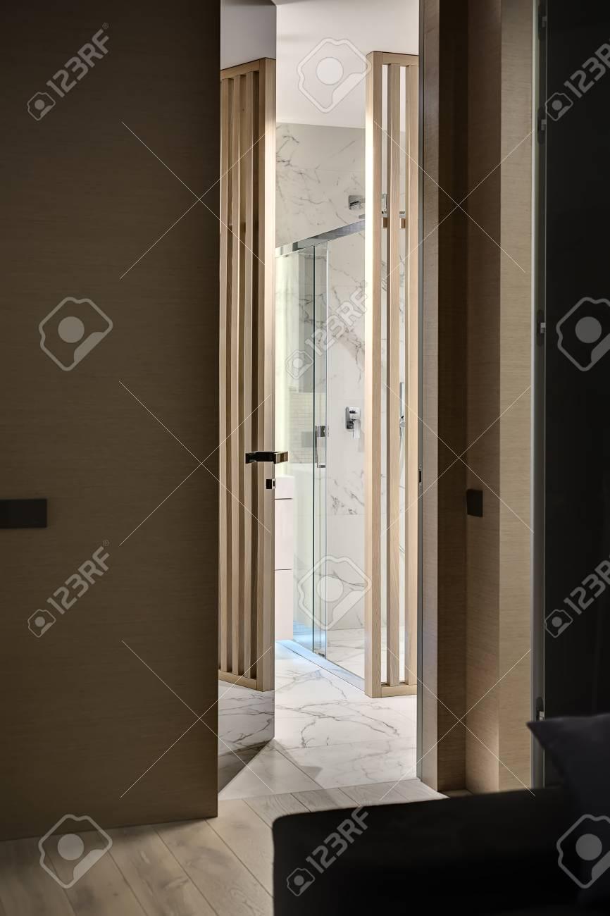 Mattonelle Simili Al Parquet ingresso al bagno negli interni in stile moderno. c'è una parete di legno  con una porta speculare, parquet sul pavimento. bagno piastrellato con