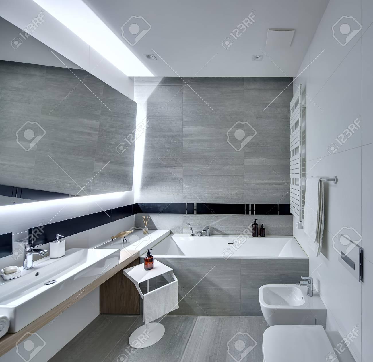 Modernes Badezimmer Mit Den Weißen Und Grauen Fliesen Gefliest. Es Gibt Ein  Weißes Waschbecken Mit Einer Seife, Einem Großen Spiegel, Einer Badewanne,  ...