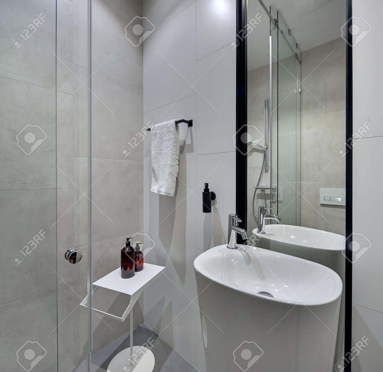 Salle de bains moderne lumière avec des carreaux blancs et crème sur les  murs et gris sur le sol. Il y a un évier blanc avec robinet chromé, douche  ...