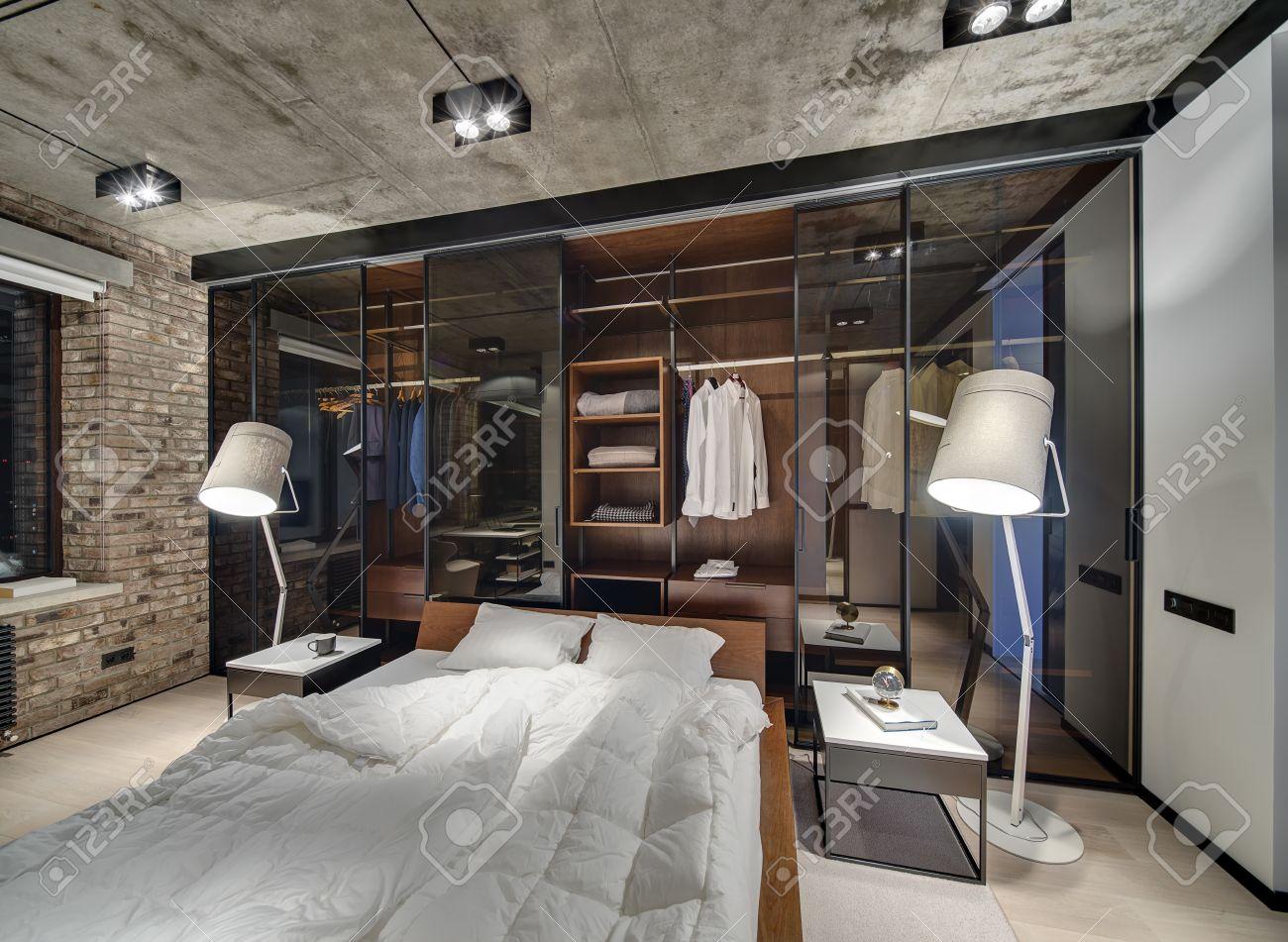 Camera da letto in stile loft con muro di mattoni e soffitto di