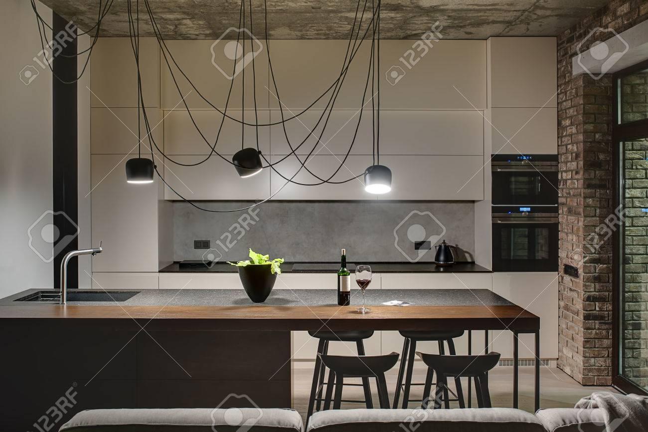 Cucina Isola Con Tavolo.Cucina In Stile Loft Con Cemento E Muri Di Mattoni C E Una Cucina Isola Con Un Lavandino Impianti E Sedie Nere Armadietti Di Luce Con Built In