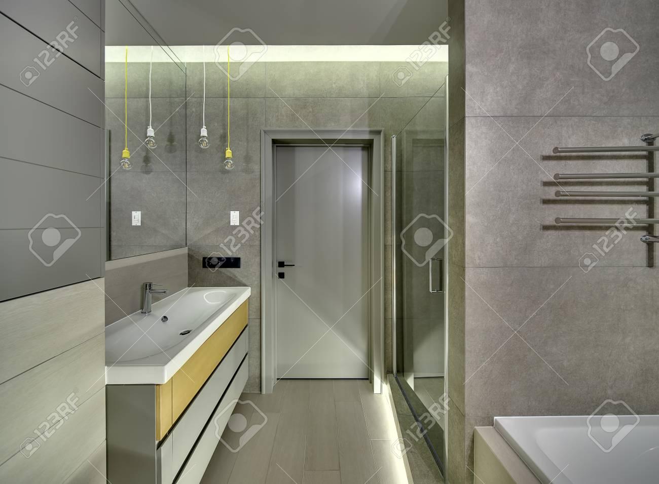 Bagno elegante in stile moderno con piastrelle sulle pareti e sul