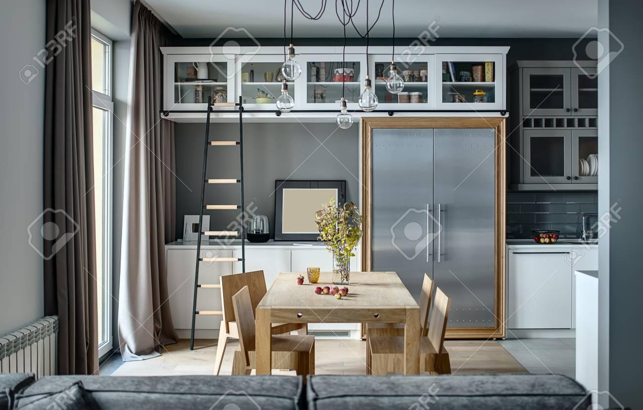 Cucina in stile moderno con pareti grigie, armadietti bianchi e mensole con  accessori. C\'è un tavolo in legno con sedie, scala scura, frigorifero con  ...