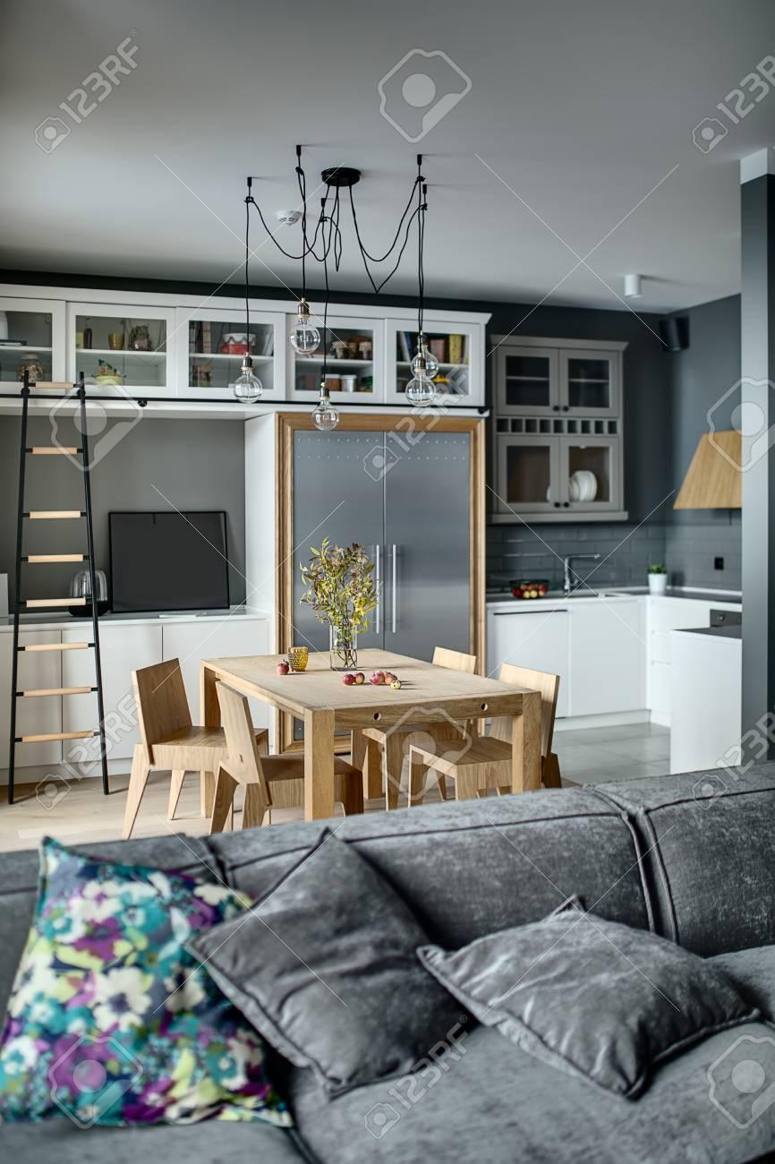 Bella cucina in stile moderno con pareti grigie, armadietti bianchi e  mensole con accessori. C\'è un tavolo in legno con sedie, scala scura, ...