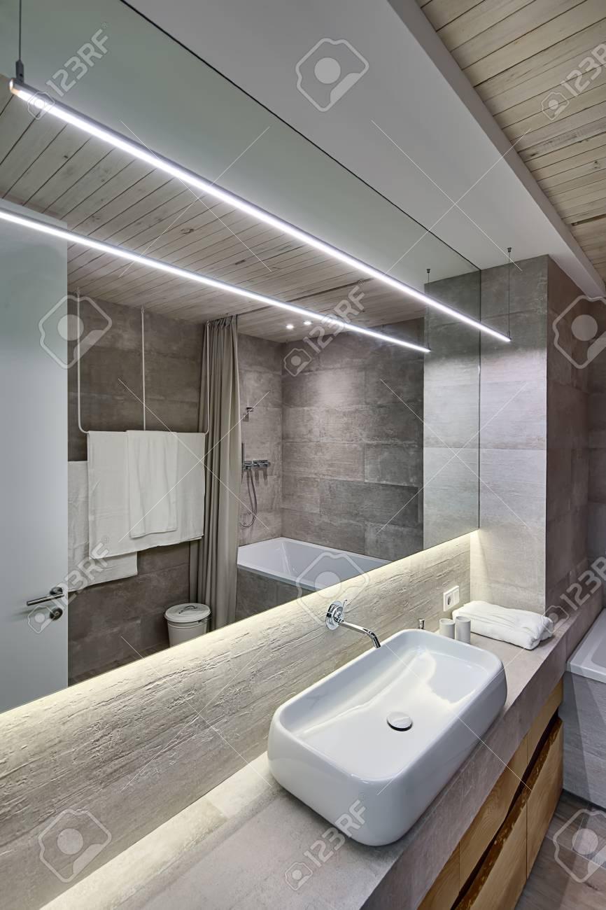 Lampada Sopra Specchio Bagno bagno contemporaneo con piastrelle strutturate e soffitto in legno. c'è un  lavandino bianco sul rack, rubinetto, armadietti di legno, specchio,