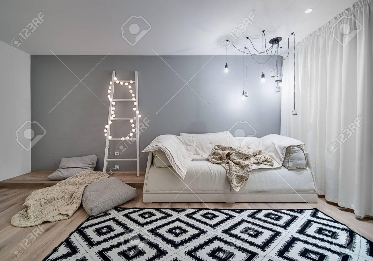 Camera in stile moderno con pareti bianche e grigie e un parquet con un  tappeto sul pavimento  C'è un divano, plaid, cuscini, scala in legno con  sfera
