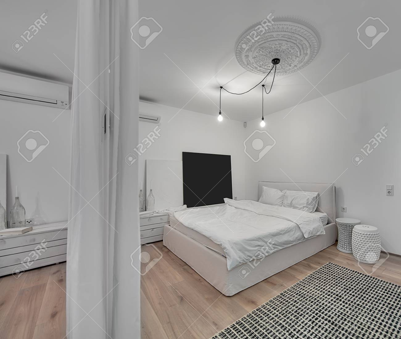 Contemporary bedroom with white walls and a parquet with a carpet..