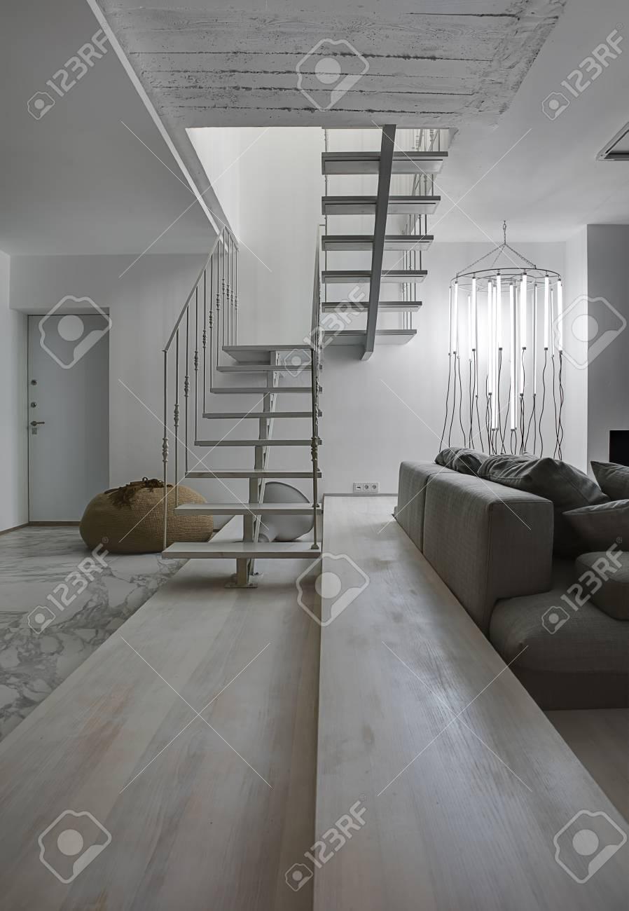 Standard Bild   Zimmer Im Modernen Stil Mit Weißen Wänden. Es Gibt Eine  Weiße Holztreppe Mit Einem Metallgeländer, Graues Sofa Mit Kissen, ...