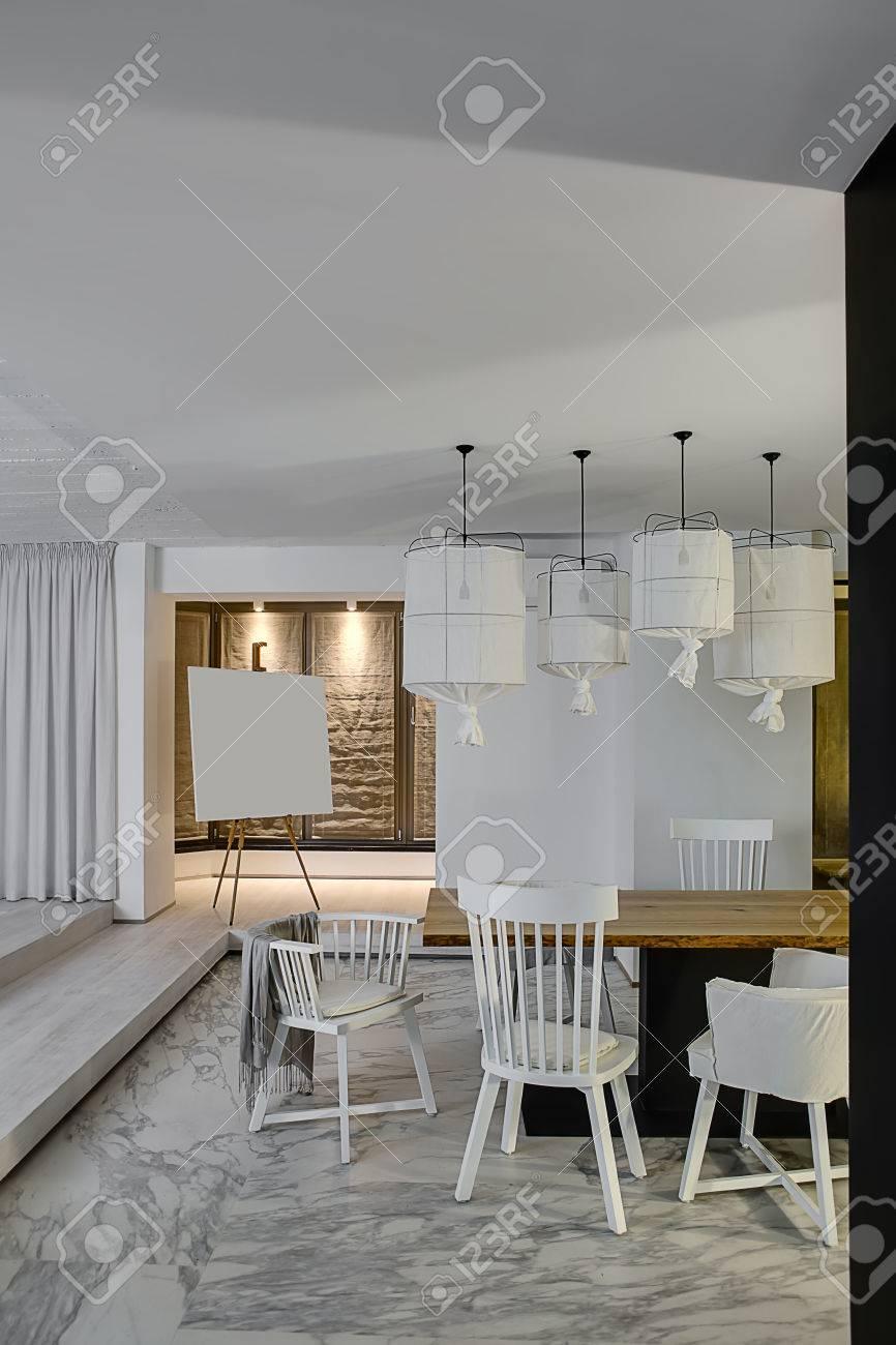 Attraktiv Zimmer In Einem Modernen Stil Mit Weißen Wänden Und Einem Parkett Mit  Grauen Fliesen Mit Mustern Auf Dem Boden. Es Gibt Einen Holztisch Mit Weißen  Stühlen, ...