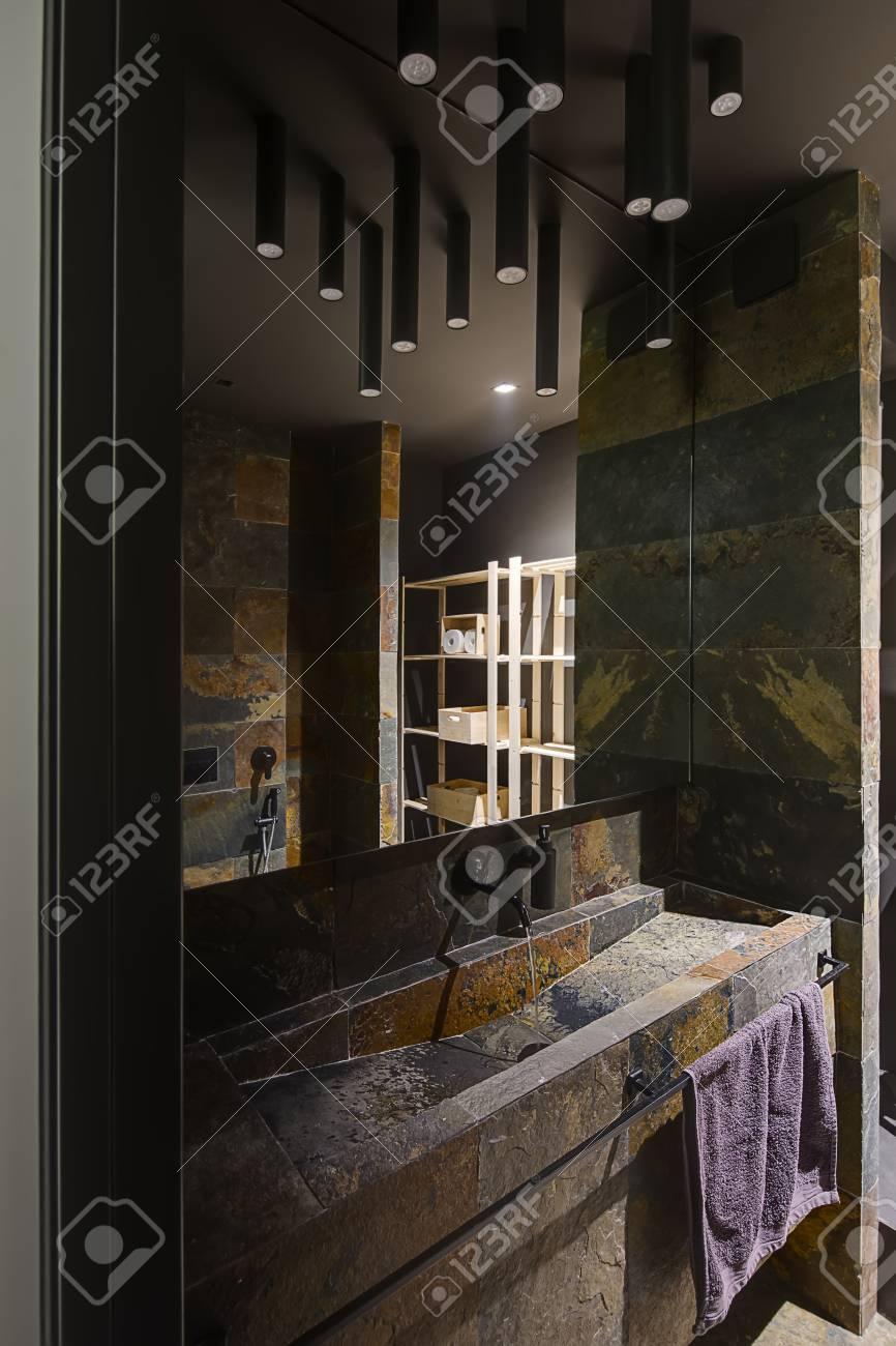 Salle de bain dans un style moderne avec un éclairage faible. Il a carrelé  avec des carreaux texturés multicolores. Il y a un évier avec robinet, ...