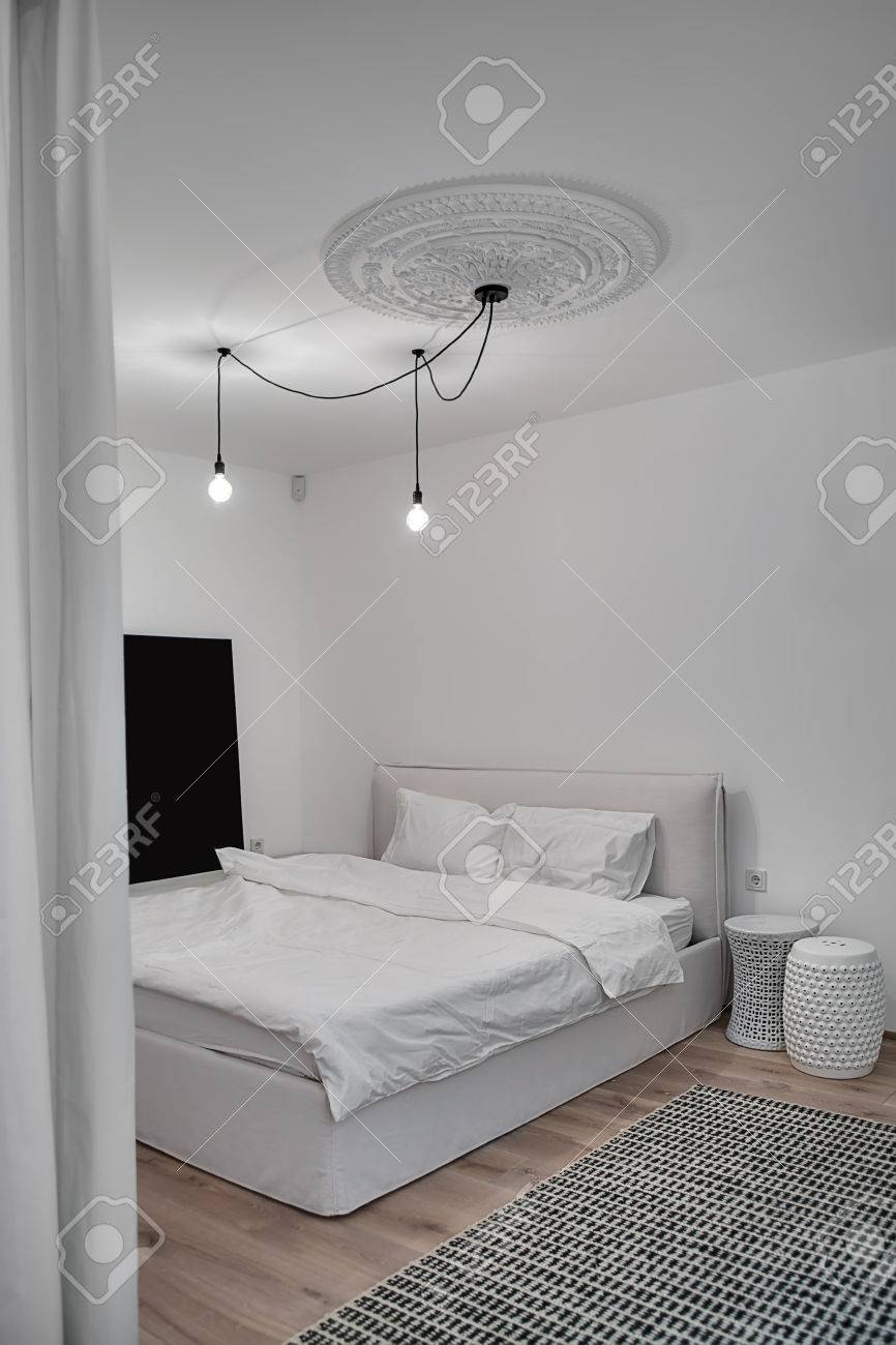 Camera da letto in stile moderno con pareti bianche e un parquet con un  tappeto sul pavimento. C\'è un letto con i cuscini bianchi e una coperta, ...