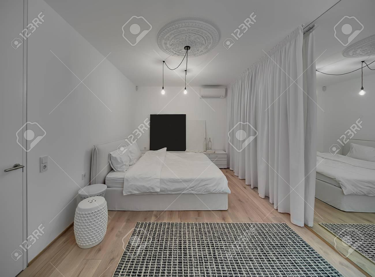Modernes Schlafzimmer Mit Weißen Wänden Und Ein Parkett Mit Einem Teppich  Auf Dem Boden. Es Gibt Ein Bett Mit Weißen Kissen Und Decke, Design  Nachttische, ...