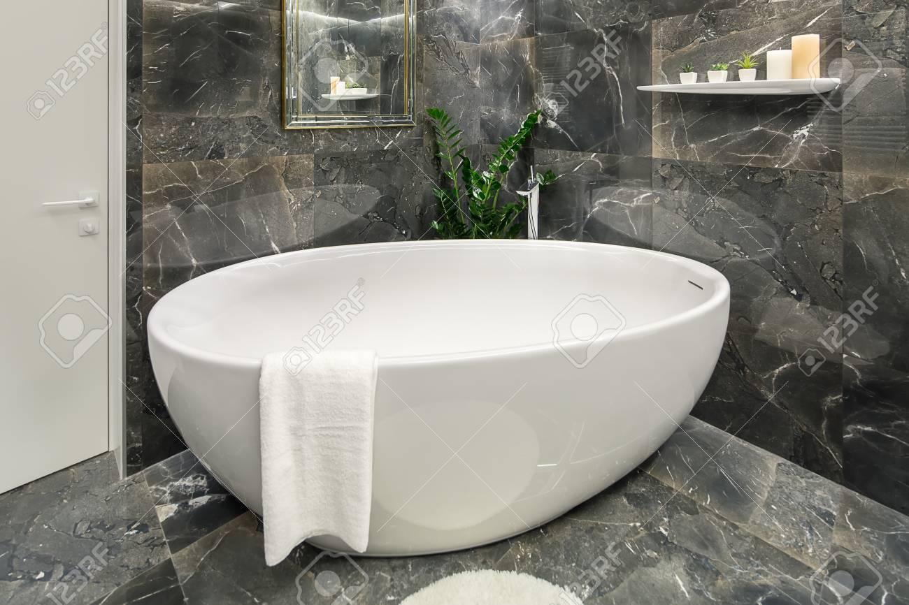 Bagno illuminato in stile moderno con tegole scure c è un grande