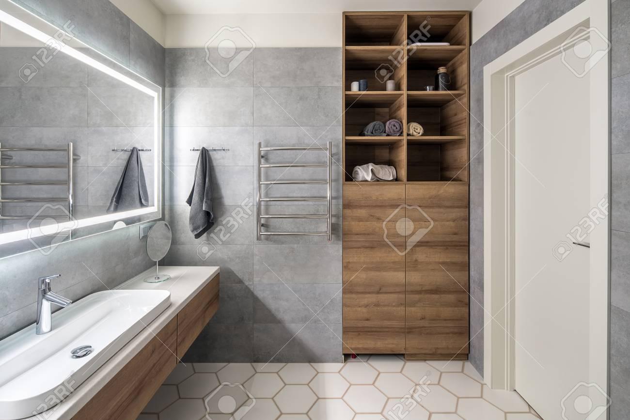 Armadietto Bagno Moderno bagno moderno con piastrelle grigie e bianche. c'è un grande specchio con  lampade luminose, tavolo con cassetti e lavandino in legno, portasciugamani