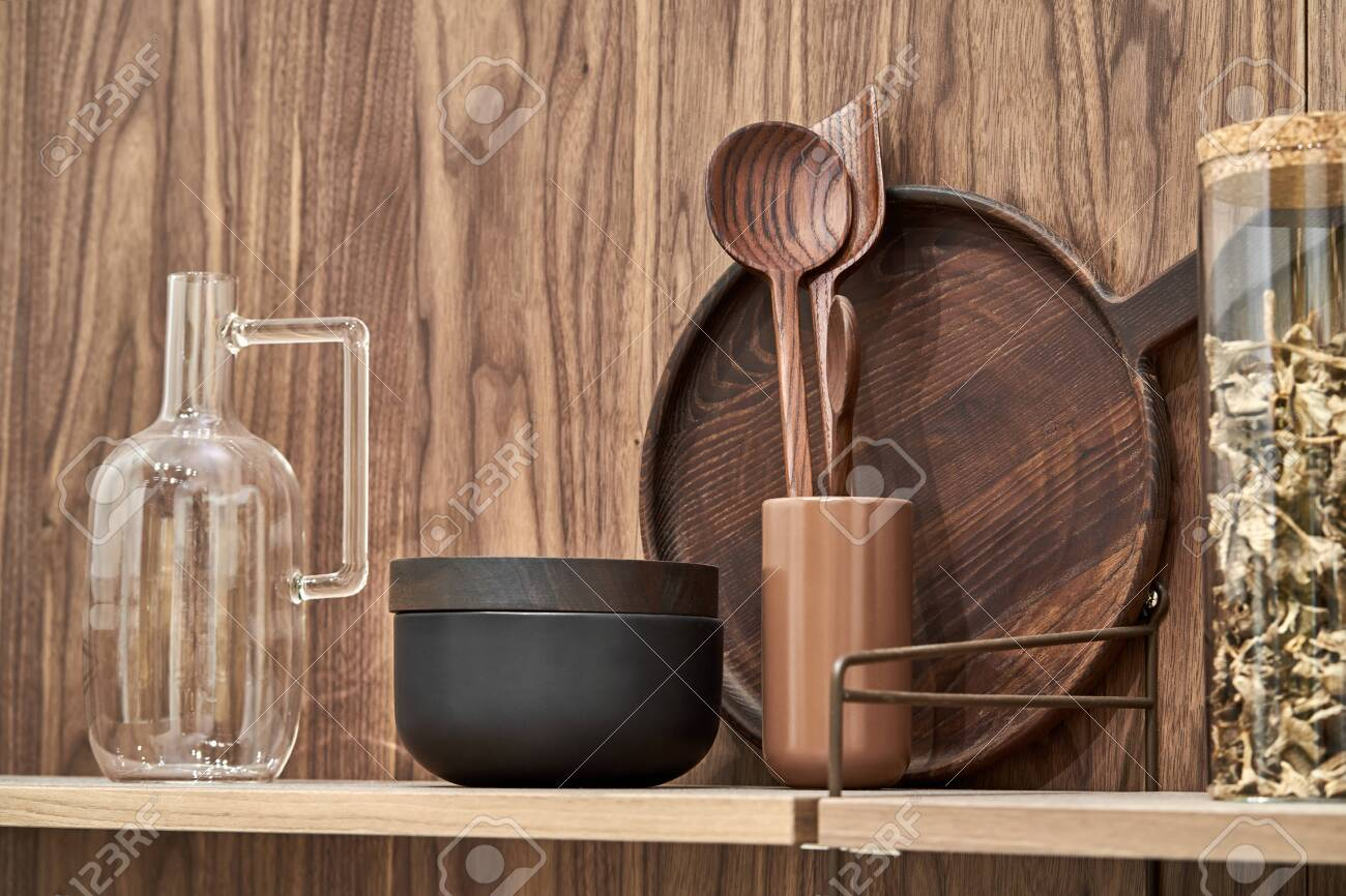 Wooden shelves with wood and ceramic utensil and glass jar and jug on the textured wall background. Closeup horizontal photo. - 143121682