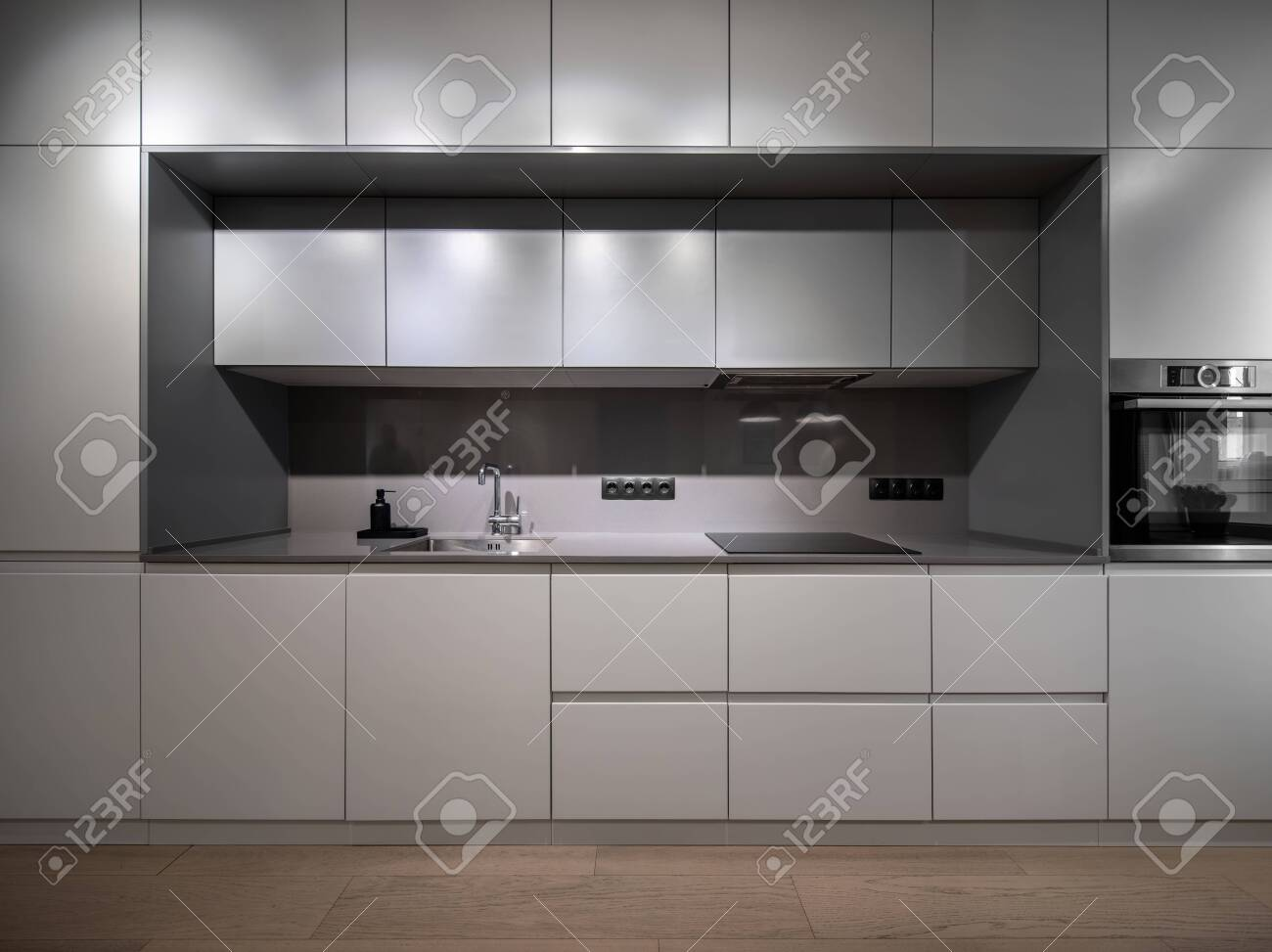 Beautiful illuminated modern gray kitchen with a parquet on the floor. There are lockers and drawers, sink with a chrome faucet, black dispenser, stove, oven, power sockets. Horizontal. - 144552645