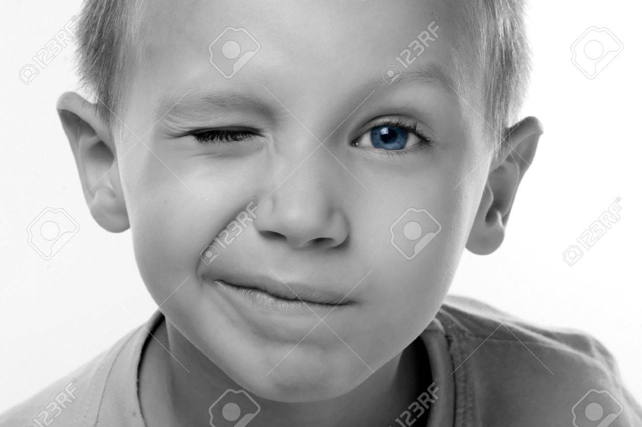 a boy with blue eyes is blinking stock photo picture and royalty