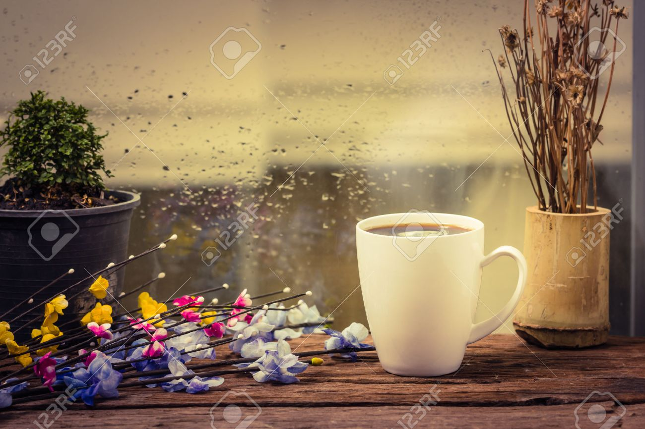 Steaming coffee cup on a rainy day window background - 31104397
